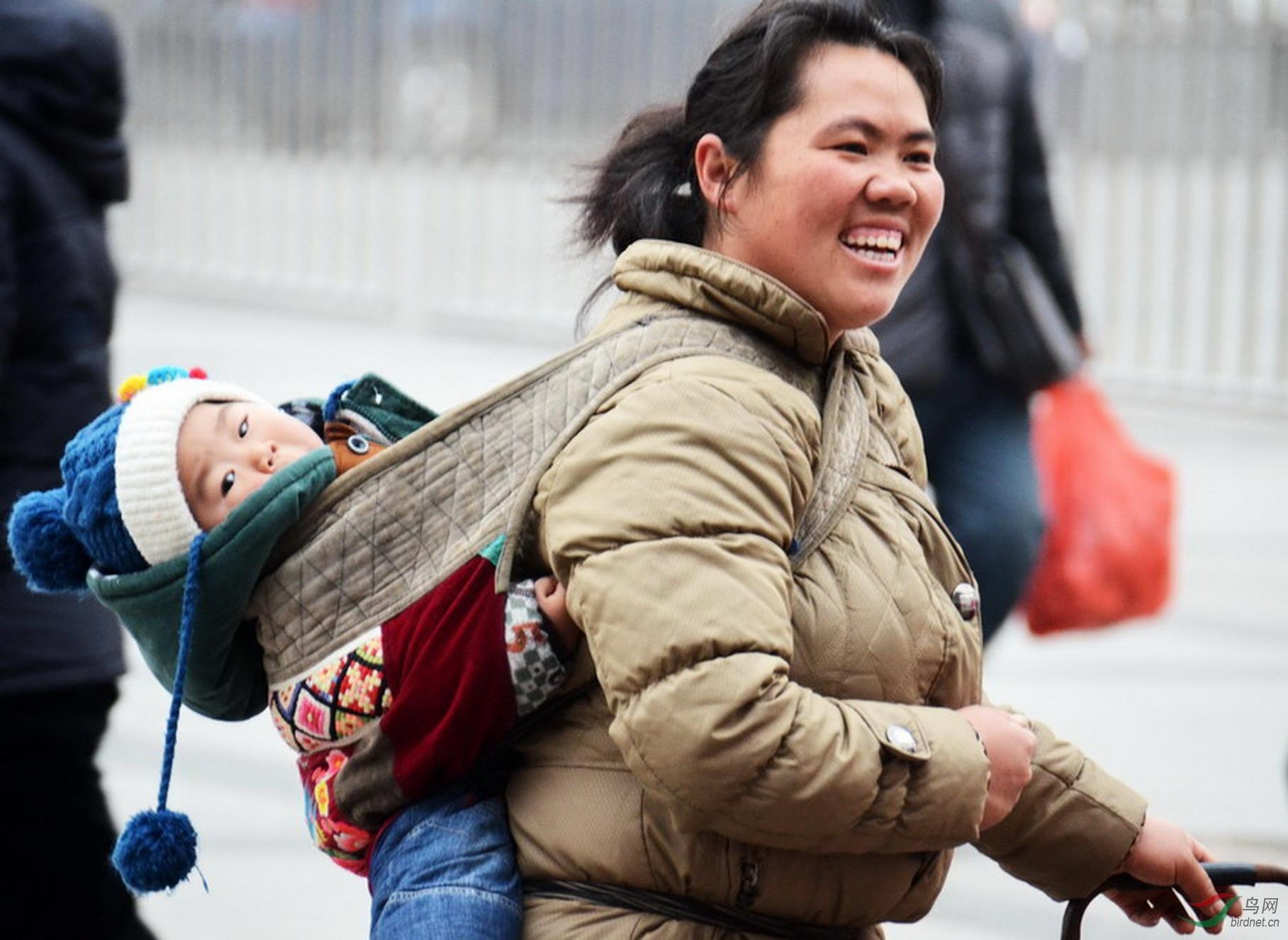 2013年春运郑州火车站广场一位母亲满面笑容身背孩子.jpg