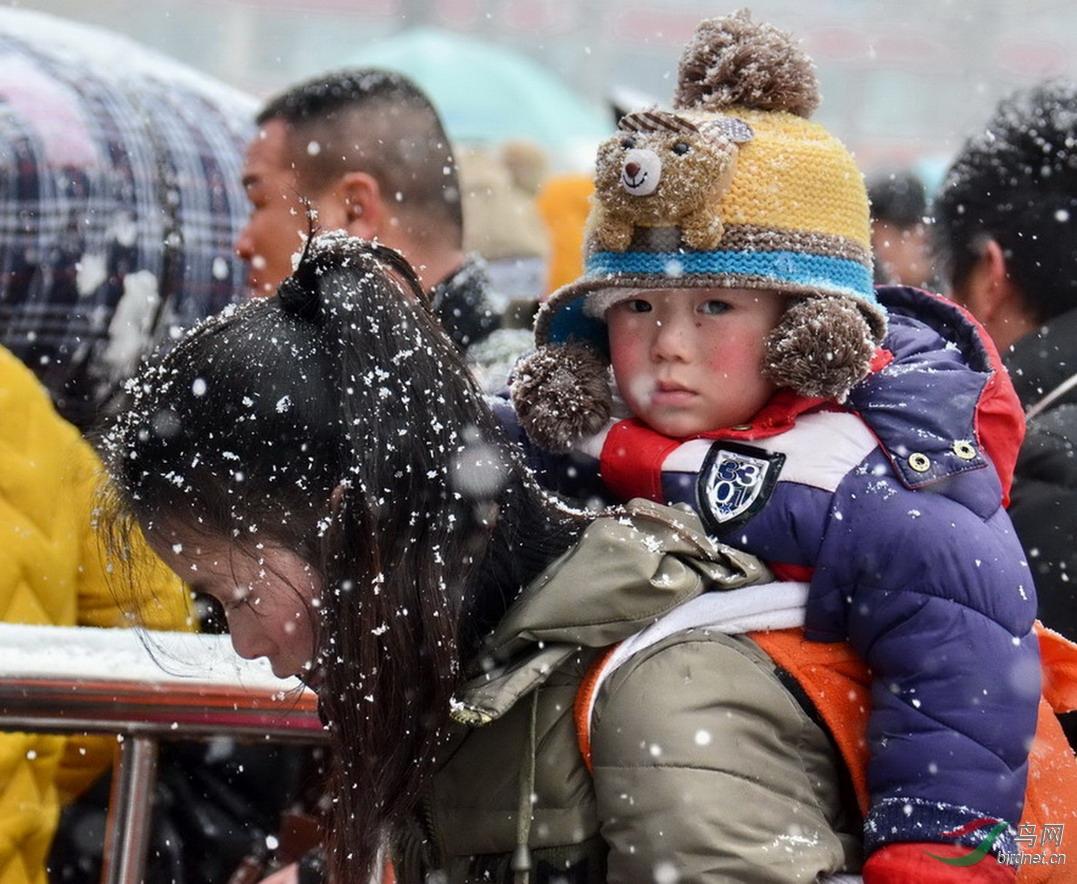 2014年春运期间郑州火车站一位母亲身背孩子冒雪进站.jpg