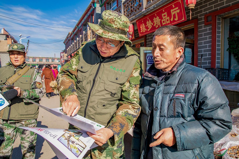 志愿者颜秉正为村农民宣传野生是动物保护法
