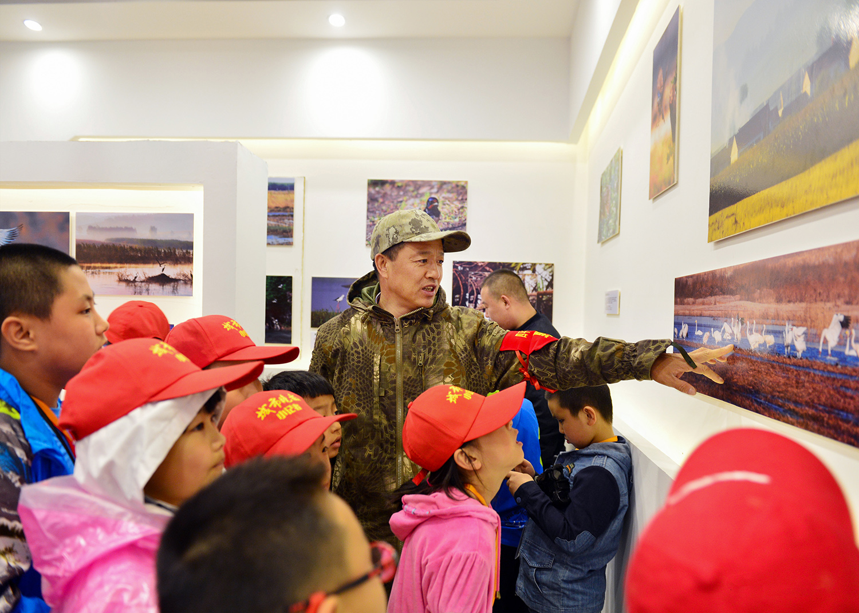 21,四平市野生动物保护志愿者联盟副会长金广山为城市晚报小记者们介绍各种鸟类的名字和鸟类的保护级别.jpg